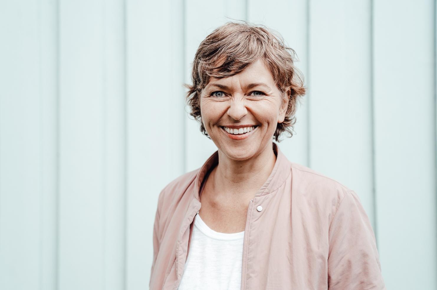 Christine Schmid trägt eine hellrosafarbende Jacke und lächelt in die Kamera.