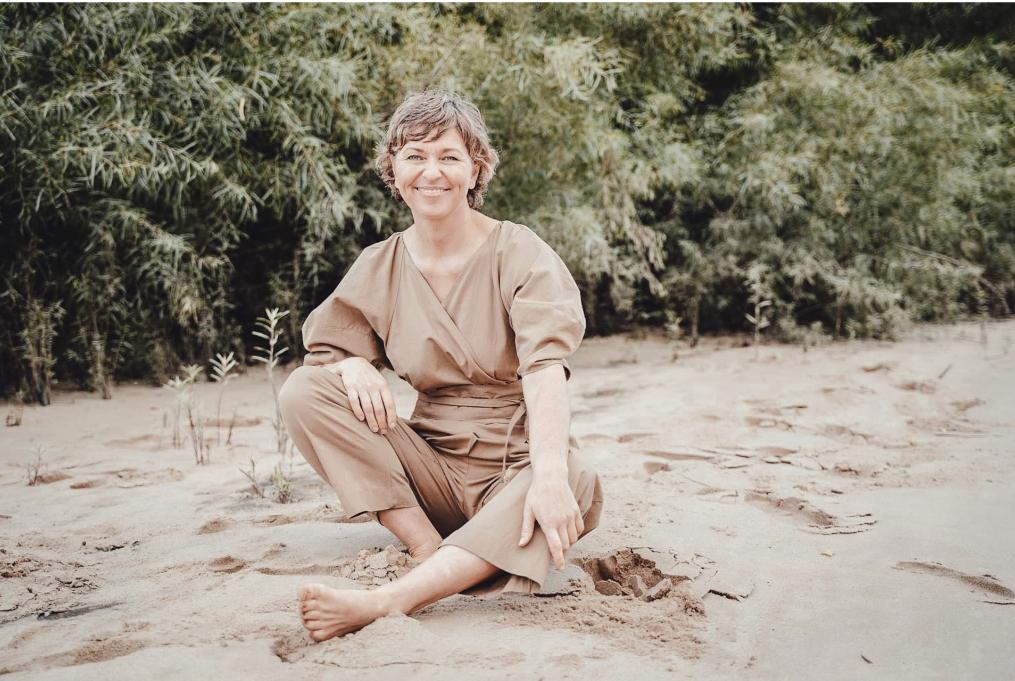 Christine Schmid trägt ein braunes Kleid, sitzend am Strand