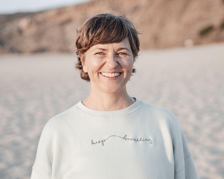 Christine Schmid am Strand lächelt direkt in die Kamera.