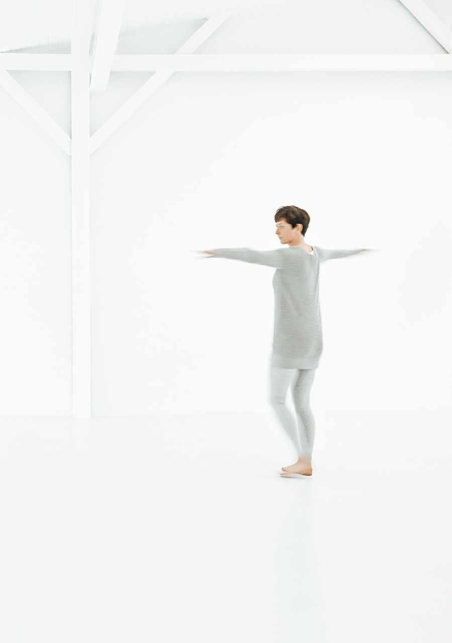 Christine Schmid, mit ausgestreckten Armen tanzend in einem hellen Raum
