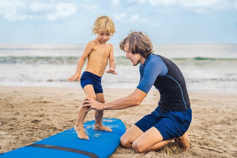 Un jeune garçon prend un cours de surf.