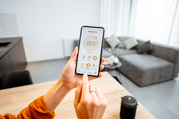 A woman controlling her temperature system with a phone having a smart home.