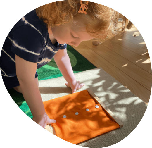 A girl with orange hair and tye dye shirt looking over an orange Montessori activity in a daycare