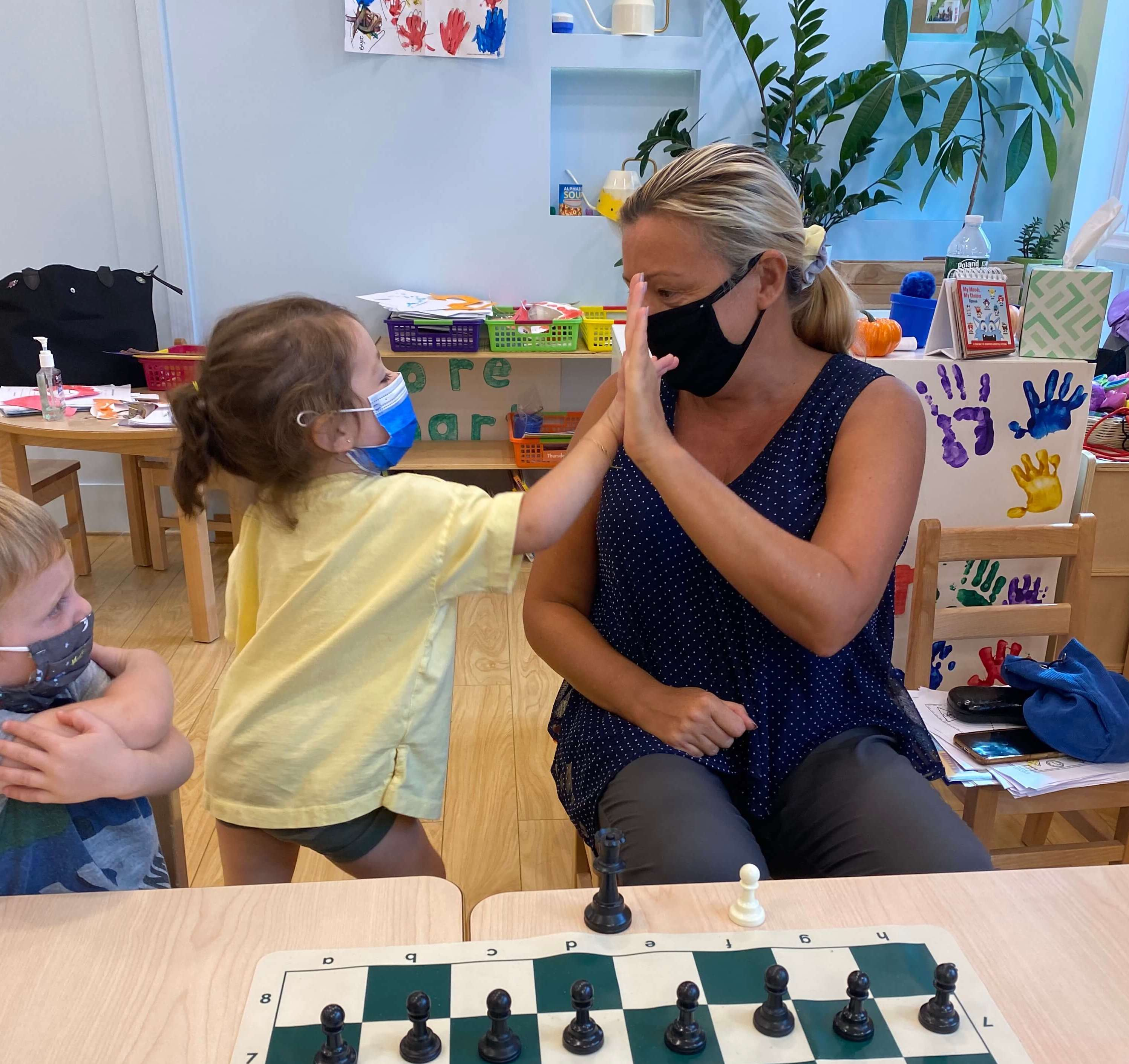 A young girl giving a high five to a teacher with a mask on as they play a game of chess in front of them on a table in a daycare