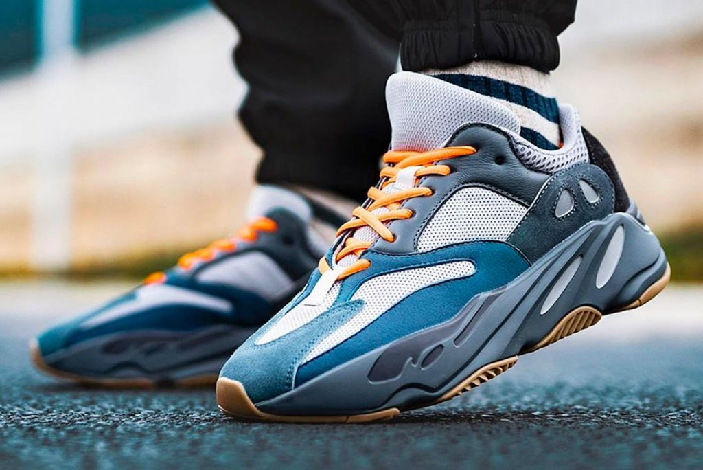 Person wearing Carbon Blue Yeezy 700 sneakers