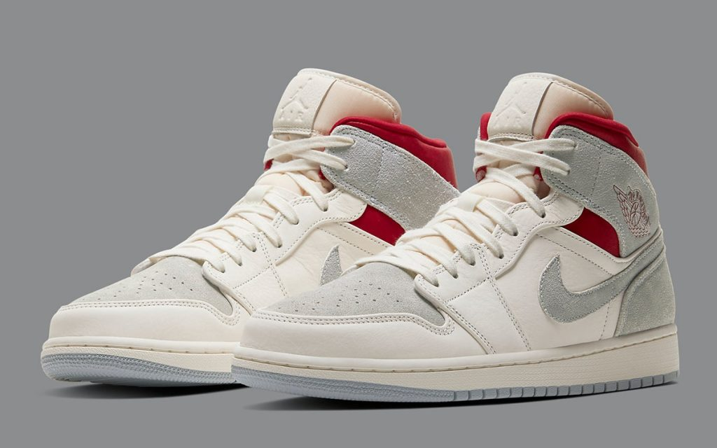 Grey, white, and red Air Jordan Mid sneakers on a grey background