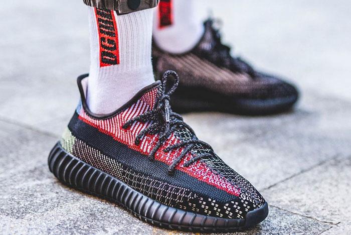Person standing on sidewalk wearing black Yeezy 350 sneakers